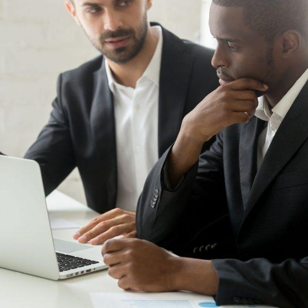 2 Business men looking at laptop