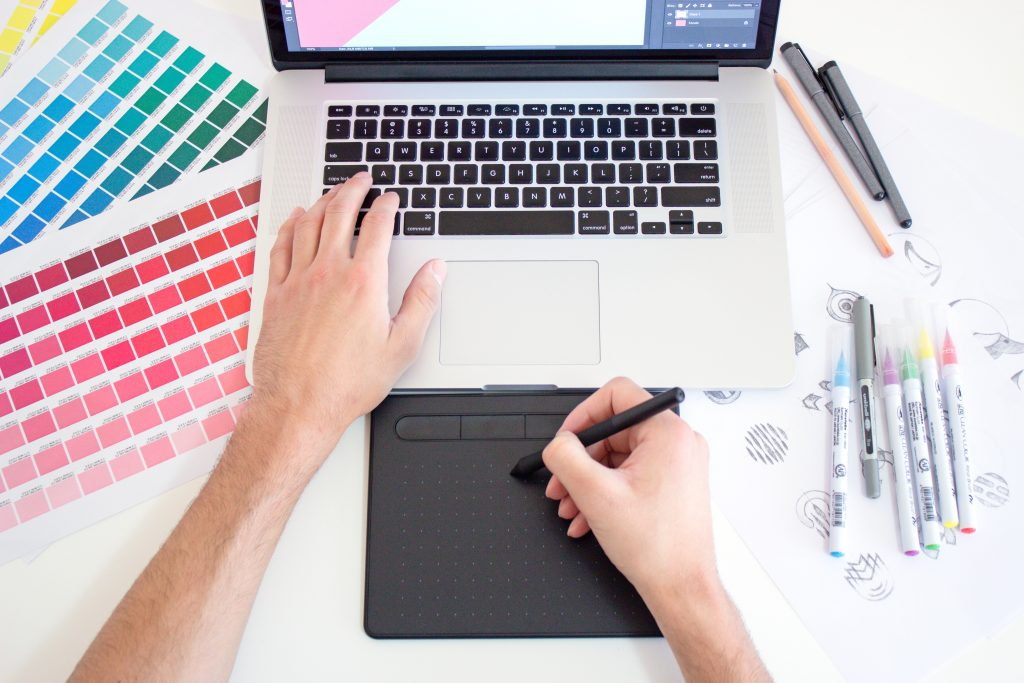 Graphic Designer using Tablet Pen and laptop