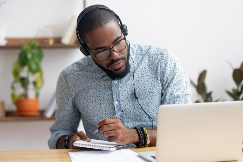 Young adult learner listening to E-Learning course with headphones